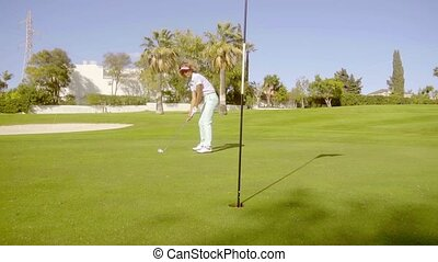 Young woman golfer putting for the hole