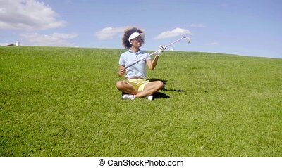 Young woman golfer sitting in the fairway