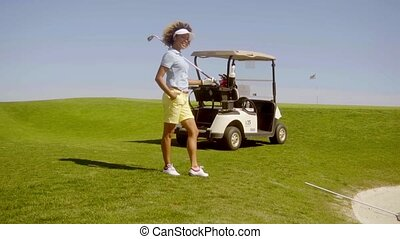 Young woman golfer standing above a sand bunker