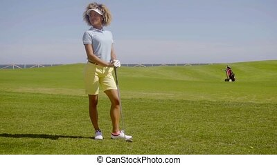 Young woman golfer standing watching