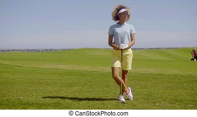 Young woman golfer standing watching - Young attractive...