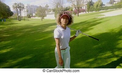 Young woman golfer striding across the fairway