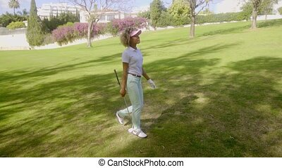 Young woman golfer striding across the fairway with a golf...