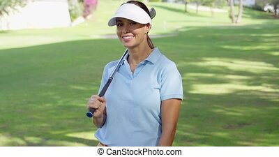 Young woman golfer strolling across the course