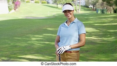 Young woman golfer strolling across the course - Young woman...