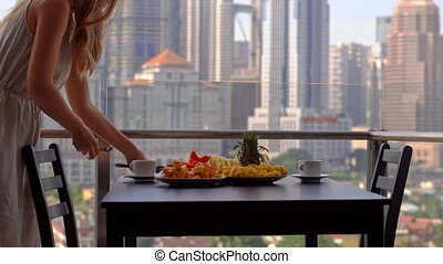 young woman governess preparing breakfast on a balcony overlooking the skyscrapers of the city center