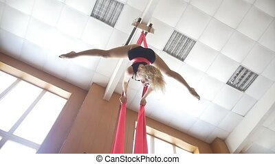 Young woman gymnast performing on aerial silk - exciting...