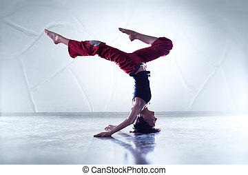 Young woman gymnast. On wall background.