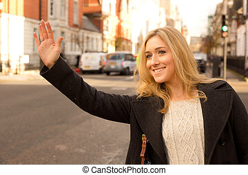 young woman hailing a taxi.