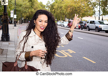 young woman hailing a taxi
