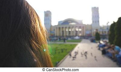 Young woman hair walking on urban street at summer sunny...