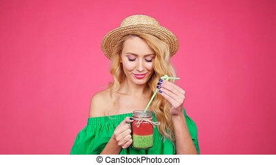 Young Woman hand holding smoothie shake against pink wall -...