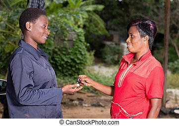 Young woman handing the key of her car to the mechanic.