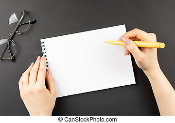 hands hold opened notebook pages with yellow pen