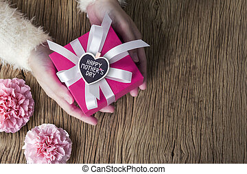 Young woman hands holding pink gift box with happy mothers day message on wood heart and carnation flower on wooden table