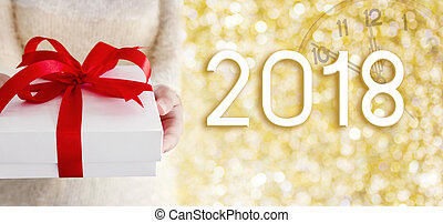 Young woman hands holding white gift box on gold bokeh with...