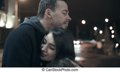 Young woman hands hugging her beloved man. Love couple in town at night embrace.