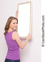 Young woman hanging mirror on wall. beautiful brunette...