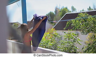 young woman hangs a towel on a rope at summer terrace