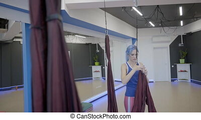 Young woman hangs fabric hammock in studio. Female stands...