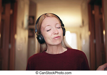 Young Woman Happily Jamming to Music on Her Bluetooth Headphones