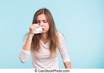 Young woman has a runny nose on blue background