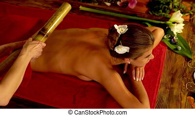 Young woman have bamboo sticks therapy massage. Top view. 4k
