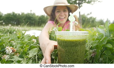 Young woman have fun in the park and drink green smoothies