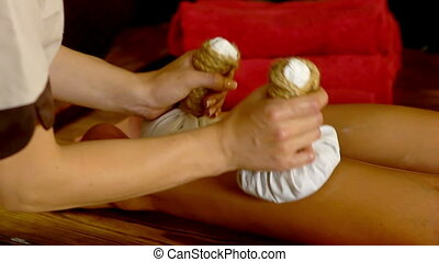 Young woman have hot foot poultice massage in spa salon.