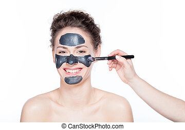 Young woman having a black charcol mask applied on her skin.
