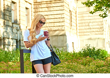 Young woman having a coffee in front of an old building