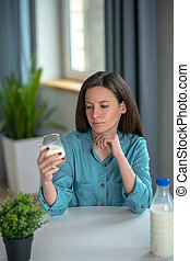 Young woman having a glass of milk in the morning