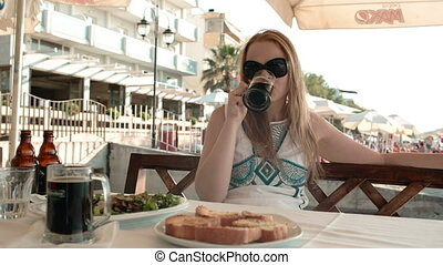 Young woman having a meal in an outdoor restaurant