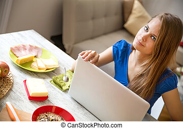 Young woman having breakfast while using a laptop computer