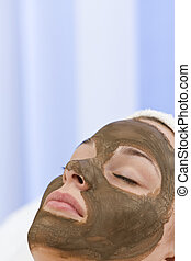 Young Woman Having Chocolate Face Mask Facial At Health Spa...