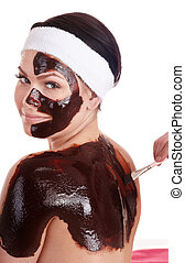 Young woman having chocolate facial mask.