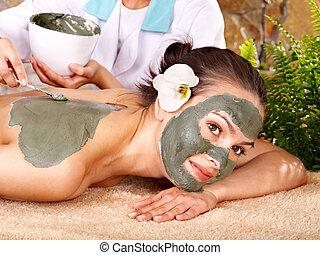 Young woman having clay body mask. - Beautiful girl having...