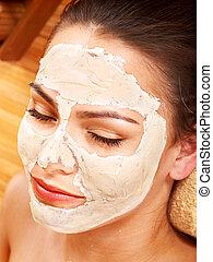 Young woman  having clay facial mask.