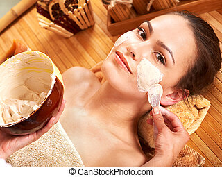 Young woman having clay facial mask. - Beautiful girl having...
