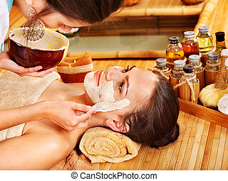 Young woman  having clay facial mask.