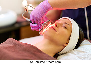 young woman having face microdermabrasion at spa