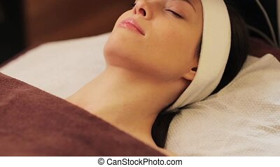 young woman having face microdermabrasion at spa - people,...