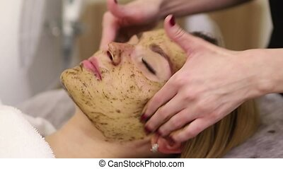 Young woman having face treatment in spa salon