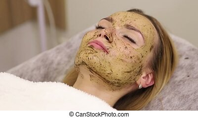 Young woman having face treatment in spa salon - Young...