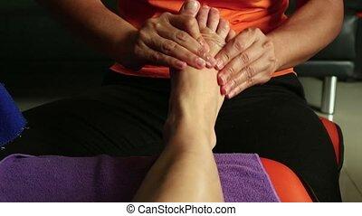 Young woman having feet massage in beauty spa salon....