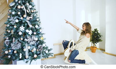 Young woman having fun and joy near christmas tree on party