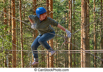 Young woman having fun in adventure rope park