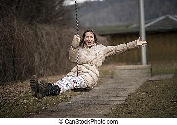 Young woman having fun on a swing