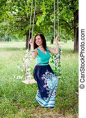 Young woman having fun swinging on a swing