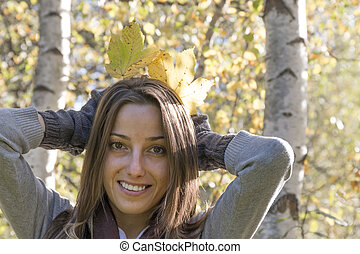 Young woman having fun with autumn leaves